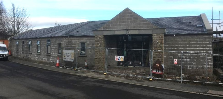 Nearly complete village hall with roof tiling on